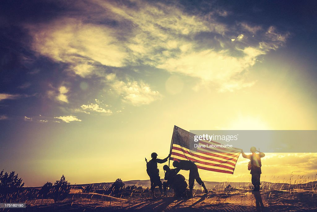 WWII Soldiers Raising The American Flag At Sunset : Stock Photo