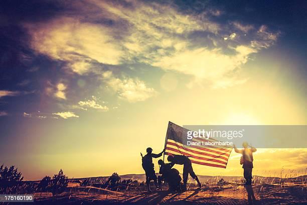 WWII Soldaten der Erhöhung der amerikanischen Flagge bei Sonnenuntergang