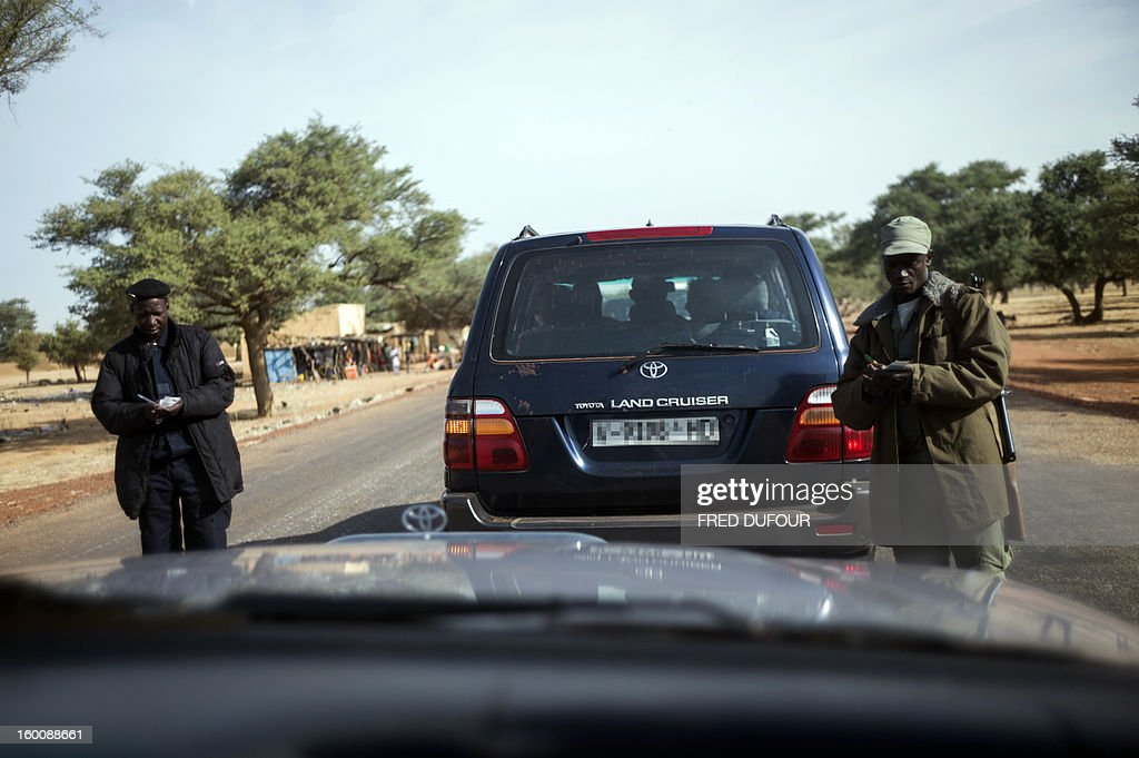Soldiers register the plates of cars carrying journalists as they arrive for an embbedment with the Malian army in a destroyed area of Konna on January 26, 2013. French-led forces today wrested control of the airport at the Islamist stronghold of Gao, 1,200 kilometres (750 miles) northeast of the Mali capital Bamako, a security source said. AFP PHOTO / FRED DUFOUR