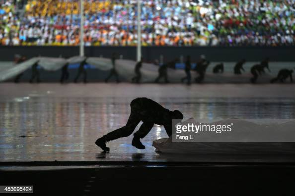 Soldiers remove water from the pitch in the rain before the opening ceremony for the Nanjing 2014 Summer Youth Olympic Games at the Nanjing Olympic...