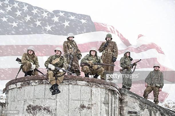 Soldati appoggiate sulla base di bombardare edificio con bandiera americana