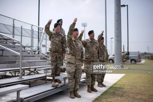 US soldiers salute as they watch members of the 1st Armoured Brigade Combat Team 1st Infantry Division take part in a transfer of authority ceremony...