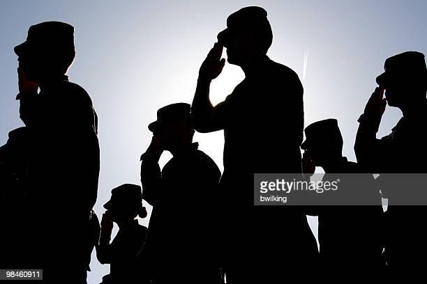 Soldados con satisfacción la bandera al atardecer