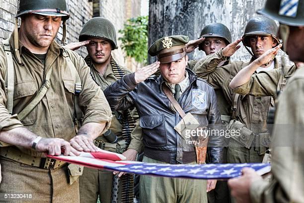 Soldados saludamos el plegable de la bandera estadounidense