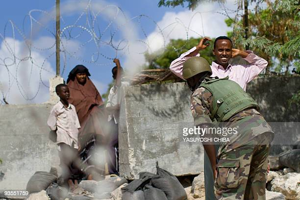 Soldiers search visitors on November 25 2009 outside the field hospital of the base of the African Union peacekeeping force in Somalia in Mogadishu...