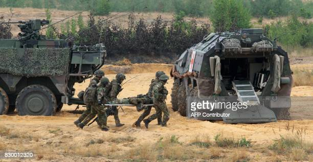 Soldiers serving in the NATO enhanced Forward Presence battalion battle group carry a comrade on a stretcher as they take part in an exercise in...