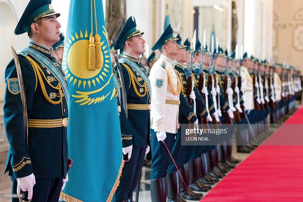 Soldiers sing the Kazakh National Anthem inside the Presidential Palace in Astana, Kazakhstan during a welcome ceremony for British Prime Minister David Cameron (not pictured) on July 1, 2013. David Cameron arrived in Kazakhstan on June 30, 2013 on the first ever trip by a serving British prime minister, hoping to boost trade ties but also promising to raise human rights concerns. AFP PHOTO/POOL/ LEON NEAL