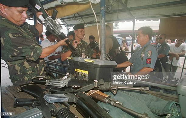 Soldiers sort out high powered firearms deposited by fellow soldiers boarding the ferry going to Jolo Sulu September 1 2000 in the Philippine Islands...