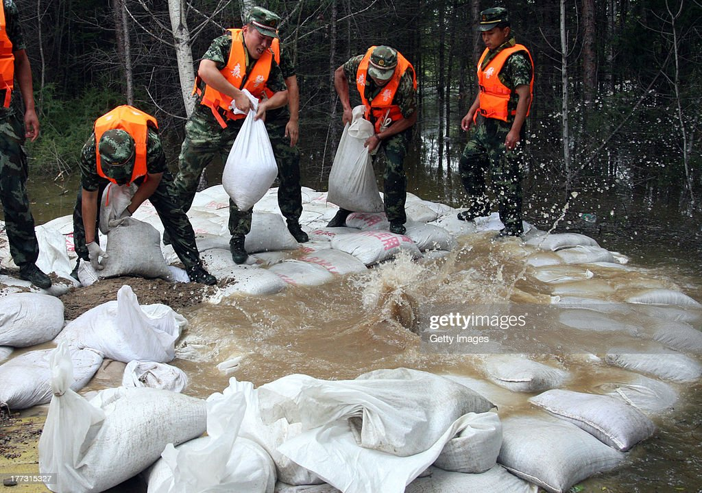 Soldiers stack sandbags to strengthen a dam on August 22, 2013 in Yichun, China. 85 people were killed and 105 others missing as rainstorms have caused havoc in northeast China's Liaoning, Jilin and Heilongjiang provinces since August 14.