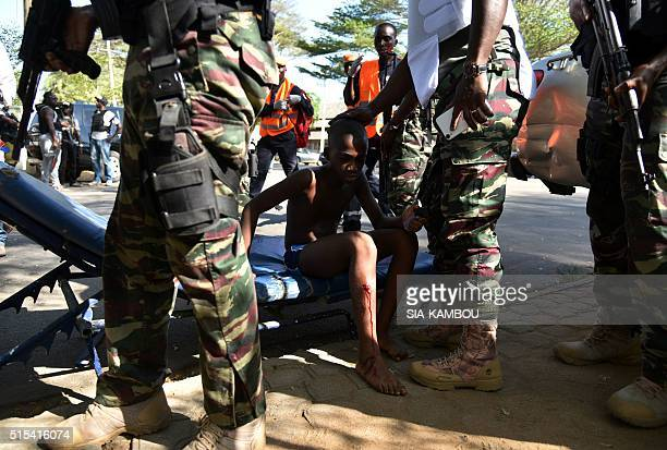 Soldiers stand around a young boy who was injured during an attack on the beach at the hotel Etoile du Sud in Grand Bassam on March 13 2016 AlQaeda's...