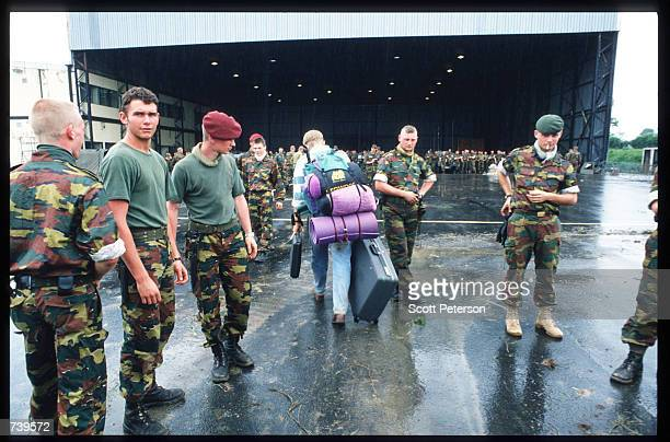 Soldiers stand around the airplane hangar to help civilians evacuate April 11 1994 in Kigali Rwanda The majority of French and Belgian nationals...