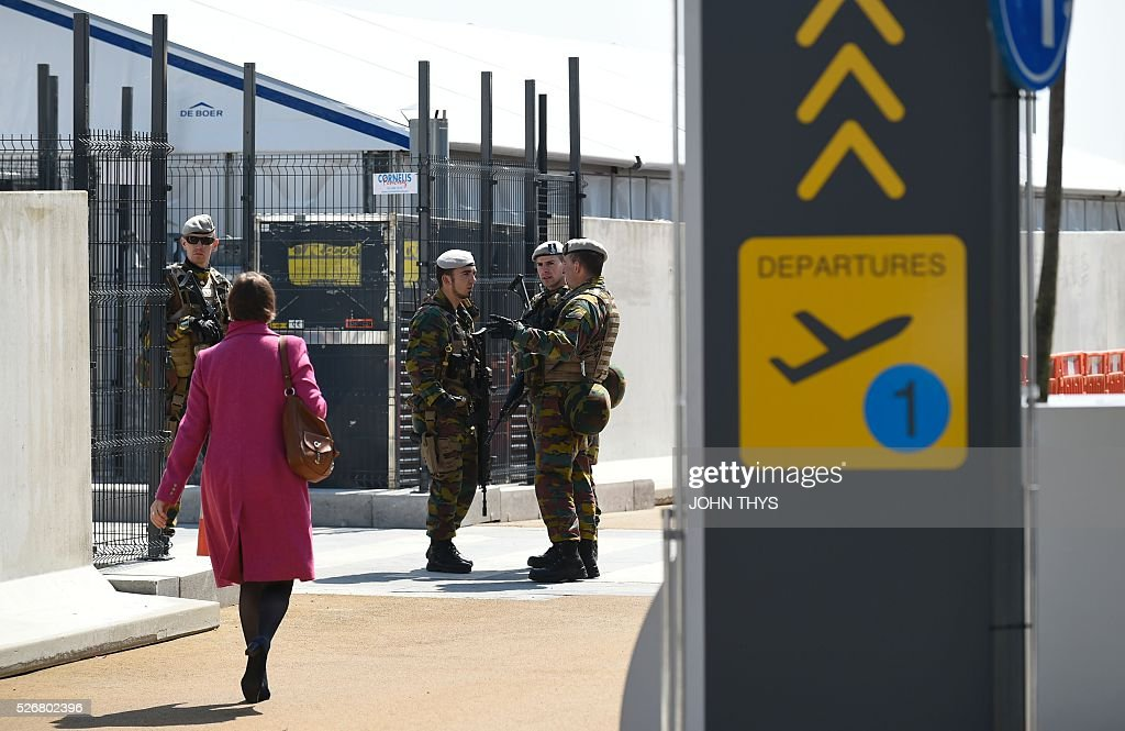 Soldiers stand as a woman walks during the partial reopening of the departure hall of Zaventem Airport in Brussels on May 1, 2016, after it was badly damaged in twin suicide attacks on March 22, that killed 16 people. A total of 32 people were killed and more than 300 wounded in coordinated suicide bombings at the airport and a metro station in central Brussels on March 22 in Belgium's worst ever terror attacks. / AFP / JOHN