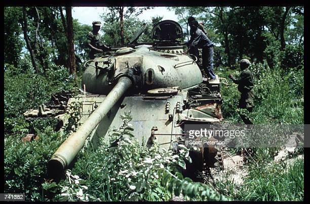 UNITA soldiers stand atop the remains of a tank January 23 1990 near Jamba Angola The National Union for the Total Independence of Angola and the...