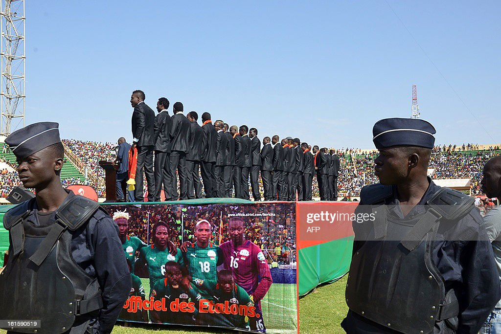 Soldiers stand guard as Burkina Faso's national football team players pose on February 12, 2013 during celebrations attended by some 40,000 people at the Stade du 4-août in Ouagadougou, two days after their first ever final in an Africa Cup of Nations tournament.