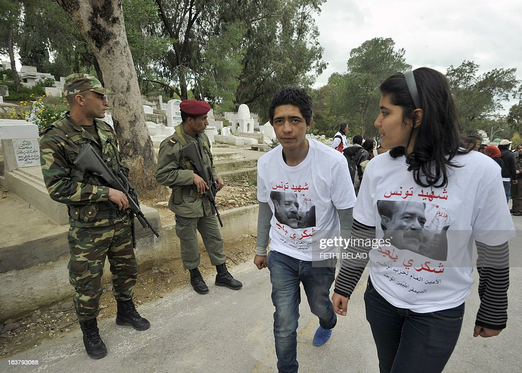 Soldiers stand guard as Tunisians gather at the tomb of anti-Islamist opposition leader Chokri Belaid (portrait on t-shirt) to mark the 40th day of mourning after his death at El-Jellaz cemetery in a suburb of Tunis on March 16, 2013. Belaid was gunned down outside his Tunis home on February 6, with the broad daylight killing sparking clashes between protesters and police and prompting the largest anti-government demonstrations since the revolution.