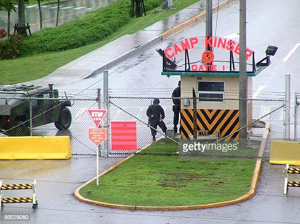 US soldiers stand guard at a gate of the US military base Kinser in Okinawa 12 September 2001 US bases in Japan stepped up security in the wake of 11...