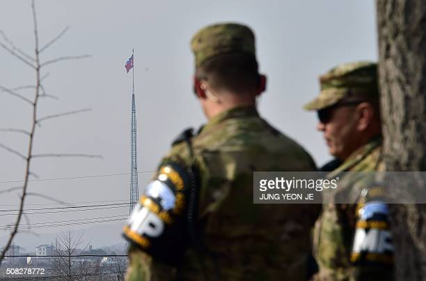 US soldiers stand guard at Taesungdong Elementary School as a North Korean flag fluttering over the propaganda village of Gijeongdong seen from South...