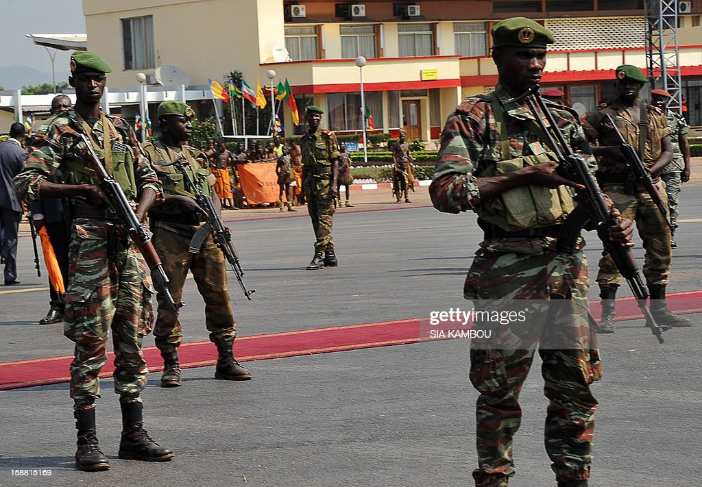 Soldiers stand guard at the airport in Bangui as the President of the Central African Republic greets the current president of the African Union and President of Benin, on December 30, 2012. Rebels in the Central African Republic who have advanced towards the capital Bangui warned they could enter the city even as the head of the African Union prepared to launch peace negotiations. Central African President Francois Bozize also stated today he was open to a national unity government after talks with rebel leaders and that he would not run for president in 2016. AFP PHOTO/ SIA KAMBOU