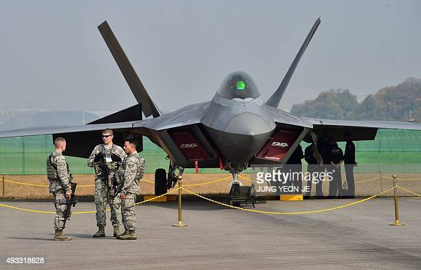 US soldiers stand guard in front of a F22 Raptor fighter jet on the tarmac during a media preview day of the Seoul International Aerospace and...