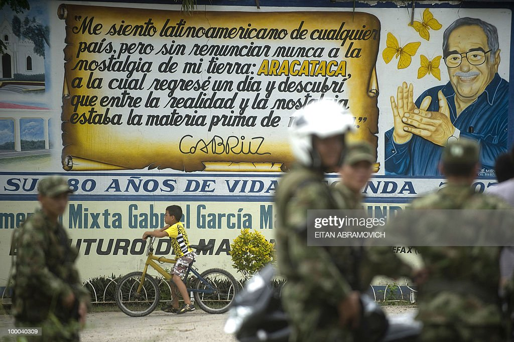 Soldiers stand guard in front of a wall with an image of Colombian Nobel Prize laureate and novelist Gabriel Garcia Marquez during a rally of Colombian presidential candidate for the for the ruling National Unity party and former Defense Minister Juan Manuel Santos (not seen) in Aracataca, Department of Magdalena, Colombia on May 20, 2010. Colombia will hold presidential elections next May 30, and according to polls, a run-off election between Colombian presidential candidate for the Green Party, Antanas Mockus and Santos will take place on June 20. AFP PHOTO/Eitan Abramovich
