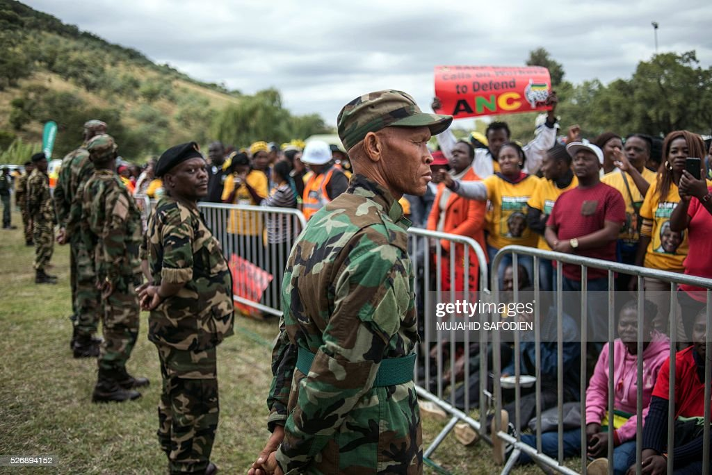 Soldiers stand guard in front of participants in the congress of South African Trade Unions (COSATU) attending the May Day rally at Mamelodi's Moreleta park on May 1, 2016 in Pretoria. Secretary General Sdumo Dlamini, South African Communist Party leader Blade Nzimande and South African President Jacob Zuma took part in the rally. / AFP / MUJAHID