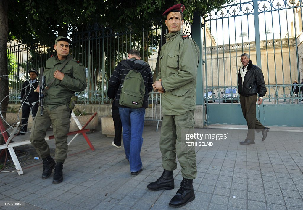 Soldiers stand guard in front of the French embassy on the Habib Bourguiba avenue as security measures are reinforced as part of the ongoing state of emergency which has been declared since the fall of ex-president on January 31, 2013 in Tunis. Tunisian President Moncef Marzouki should decide today wether to continue the state of emergency or not.