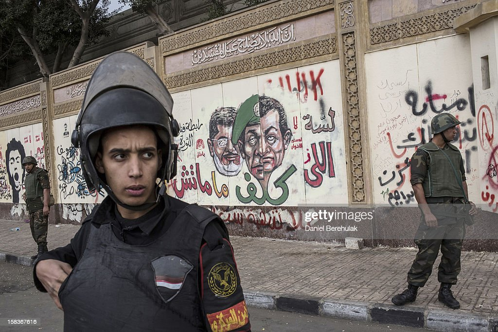 Soldiers stand guard in front of the presidential palace as anti-scaf graffiti is seen on the wall on December 14, 2012 in Cairo, Egypt. Opponents and supporters of Egyptian President Mohamed Morsi staged final rallies in Cairo ahead of tomorrow's referendum vote on the country's draft constitution that was rushed through parliament in an overnight session on November 29. The country's new draft constitution, passed by a constitutional assembly dominated by Islamists, will go to a referendum vote on December 15.