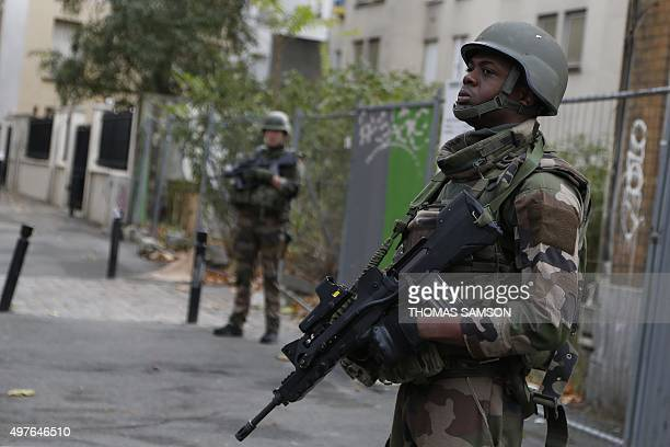 Soldiers stand guard in the northern Paris suburb of SaintDenis city center on November 18 as French Police special forces raid an appartment hunting...