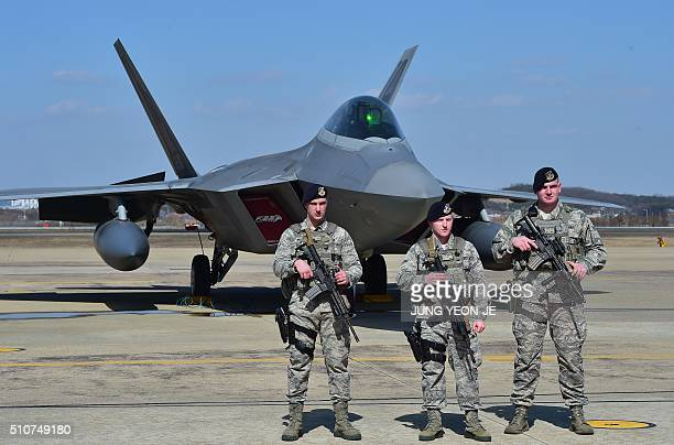 US soldiers stand guard near a US F22 stealth fighter at the Osan Air Base in Pyeongtaek south of Seoul on February 17 2016 The radarevading aircraft...