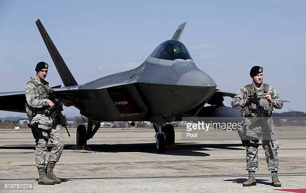 S soldiers stand guard near a US F22 stealth fighter at the Osan Air Base on February 17 2016 in Pyeongtaek South Korea US military has deployed four...