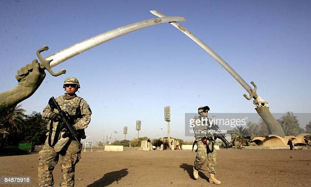 S soldiers stand guard near the two sword monument at the heavily fortified green zone area on February 18 2009 in Baghdad Iraq The Shuhada fish...