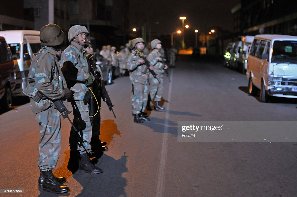 Soldiers stand guard outside Jeppestown hostel as police units conduct raids inside the hostels on April 21 2015 in Johannesburg South Africa After...