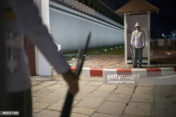 Soldiers stand guard outside The Grand Palace as people gather to pay their respects to Thailand's late King Bhumibol Adulyadej as the city prepares...