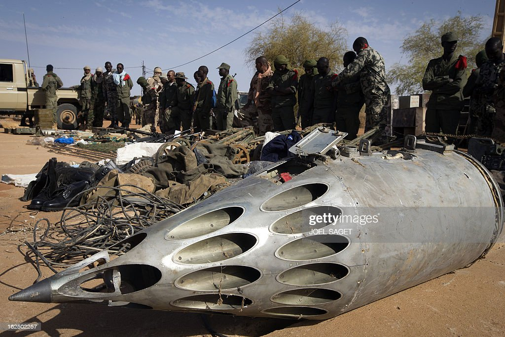 Soldiers stand in front of a rocket pod launcher and weapons seized from Islamist fighters exhibited by the Malian army in the centre of Gao on February 24, 2013. Tuareg militias battled Arab rebels in northern Mali Saturday, while French jets, US drones and Chad's elite desert forces were also in action in a major push to stamp out resistance from pockets of Islamist fighters. After recapturing the north's cities from the Al Qaeda groups that had controlled them since April 2012, the six-week-old French-led offensive took the fight to the retreating Islamist insurgents' toughest desert bastions. AFP PHOTO /JOEL SAGET