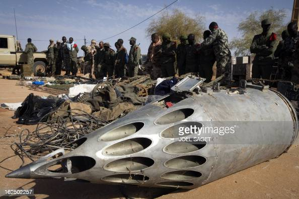 Soldiers stand in front of a rocket pod launcher and weapons seized from Islamist fighters exhibited by the Malian army in the centre of Gao on...