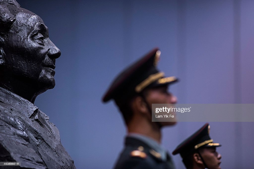 PLA soldiers stand in front of a sculpture featuring former Chinese leader Deng Xiaoping during the Exhibition of the 110th anniversary of the birth...