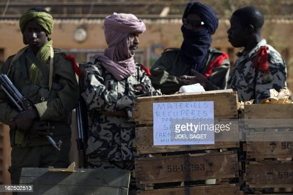 Soldiers stand in front of ammunitions seized from Islamist fighters exhibited by the Malian army in the centre of Gao on February 24 2013 Tuareg...