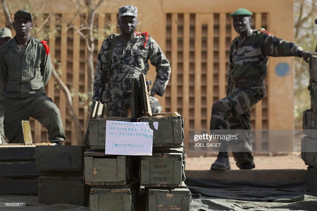 Soldiers stand in front of weapons and ammunitions seized from Islamist fighters exhibited by the Malian army in the centre of Gao on February 24, 2013. Tuareg militias battled Arab rebels in northern Mali Saturday, while French jets, US drones and Chad's elite desert forces were also in action in a major push to stamp out resistance from pockets of Islamist fighters. After recapturing the north's cities from the Al Qaeda groups that had controlled them since April 2012, the six-week-old French-led offensive took the fight to the retreating Islamist insurgents' toughest desert bastions. (placard reads : Material collected by Young Patriots - Ammunition).