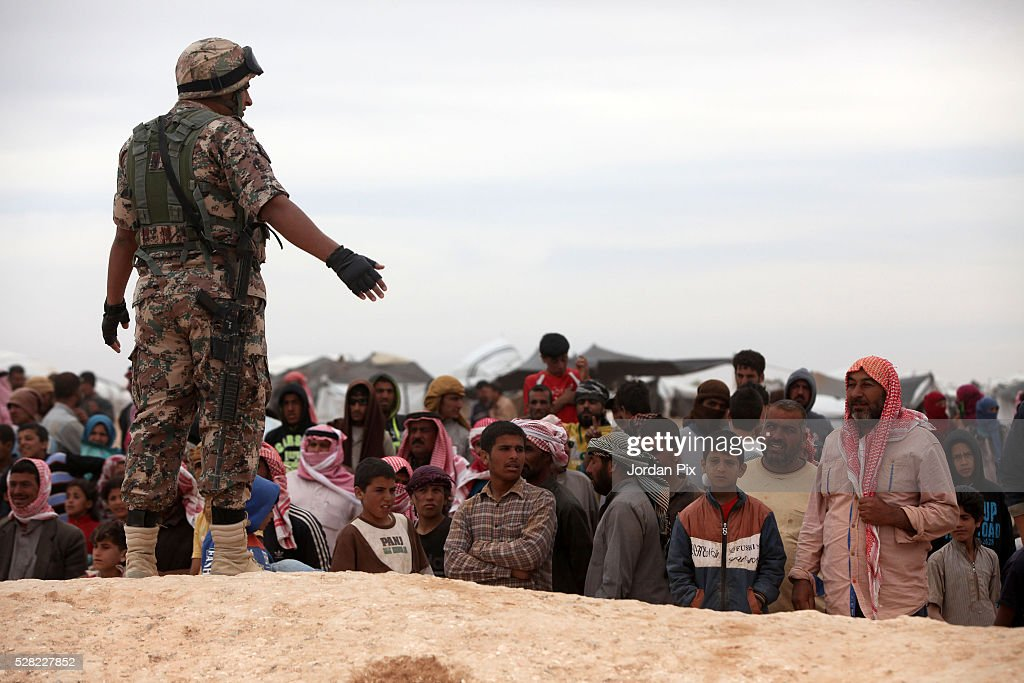 Soldiers stand near Syrian refugees who have arrived at the Jordanian military crossing point of Hadalat at the border with Syria after a long walk through the Syrian desert on May 4, 2016 in Hadalat, Jordan. Coming from the cities of Raqaa, Deir Al-Zor and Hama, roughly 300 hundred refugees crossed into Jordan at Hadalat on Wednesday, while over 5000 refugees crossed in the last four days coming from Aleppo.