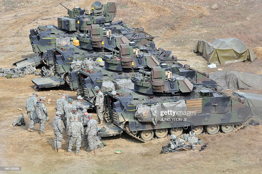 US soldiers stand next to Bradley armored vehicles at a military training field in the border city of Yeoncheon, northeast of Seoul, on April 9, 2013. North Korea said on April 9 the Korean peninsula was headed for 'thermo-nuclear' war and advised foreigners in South Korea to consider evacuation -- a warning that was largely greeted with indifference.