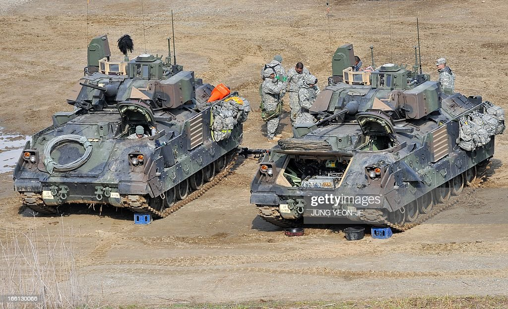 US soldiers stand next to Bradley armored vehicles at a military training field in the border city of Yeoncheon, northeast of Seoul, on April 9, 2013. North Korea said on April 9 the Korean peninsula was headed for 'thermo-nuclear' war and advised foreigners in South Korea to consider evacuation -- a warning that was largely greeted with indifference. AFP PHOTO / JUNG YEON-JE