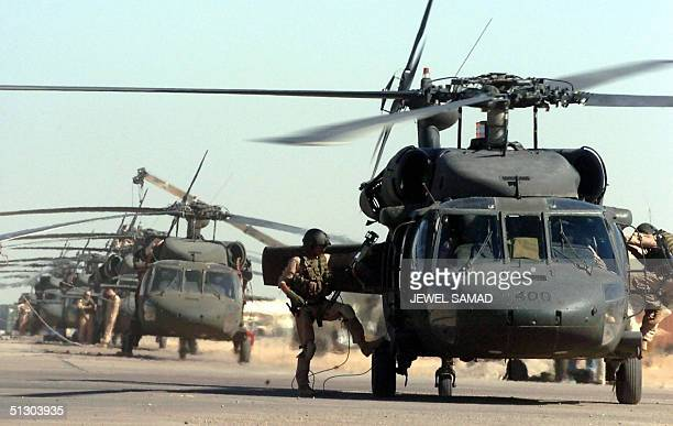 US soldiers stand next to their blackhawk helicopters at a US base in Iraqi northern town of Balad 14 September 2004 Iraqi President Ghazi alYawar...