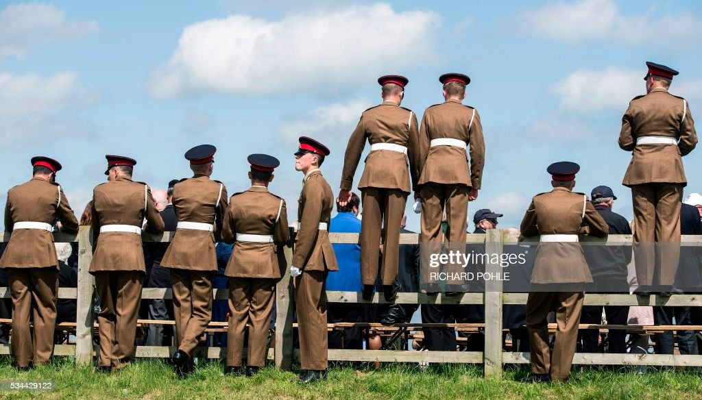 Soldiers stand on a fences as they await the arrival of Britain's Queen Elizabeth II (C), as she reviews the weapons of the Royal Artillery at Knighton Down, Larkhill on Salisbury plain, southern England on May 26, 2016. 2016 marks the Tercentenary of the formation of the Royal Artillery when, on 26 May 1716, by Royal Warrant of King George 1, two companies of artillery were formed at Woolwich in London, alongside the guns, powder and shot located in the Royal Arsenal. / AFP / RICHARD