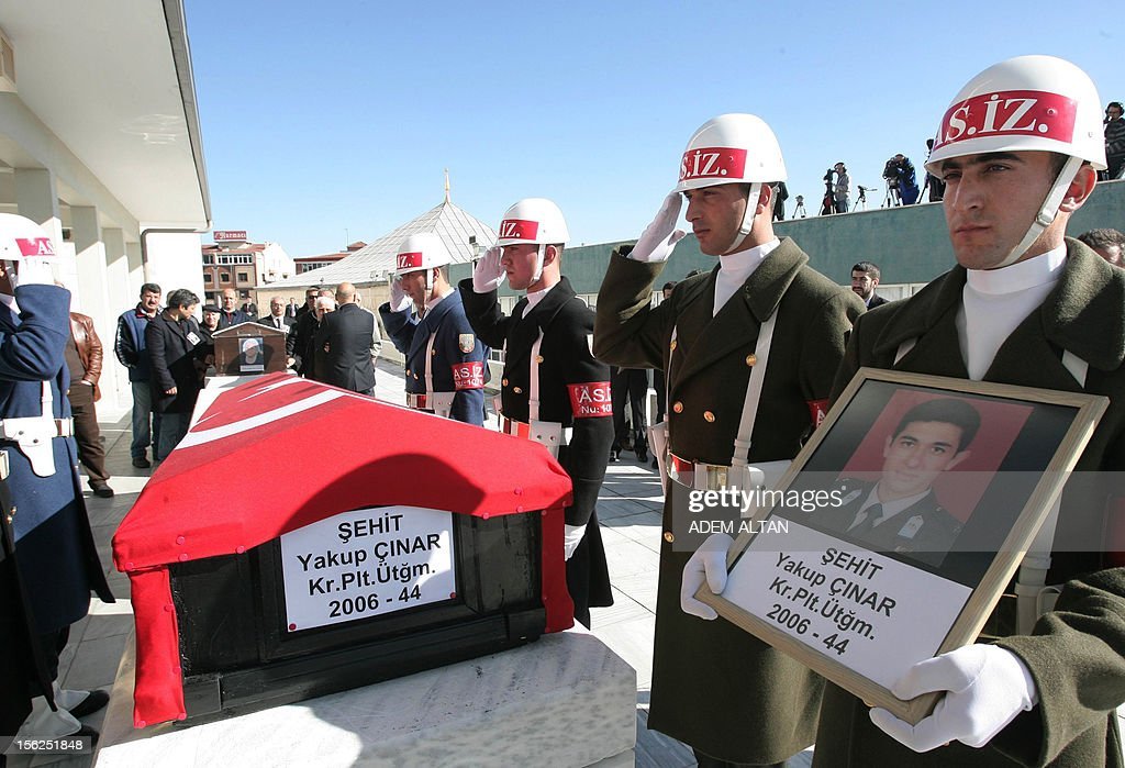 Soldiers stand still by the flag-covered coffin of army officer Yakup Cinar, one of 17 Turkish soldiers who were killed in a helicopter crash early on November 9, 2012 in Siirt province, during his funeral in Ankara on November 12, 2012. The Turkish military helicopter crashed on November 9, 2012 in bad weather in the southeastern city of Siirt, killing all 17 troops on board, local officials said.