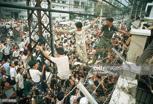 Soldiers stopping people in the crowded street from climbing over the walls of the United States Embassy in Saigon South Vietnam