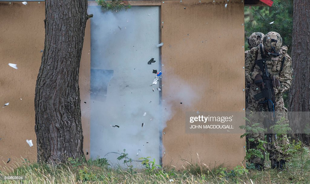 Soldiers take cover as they blow open a door during a drill at the headquarters of the 33rd Panzergrenadier bataillon in Neustadt am Ruebenberge on June 29, 2016. / AFP / JOHN