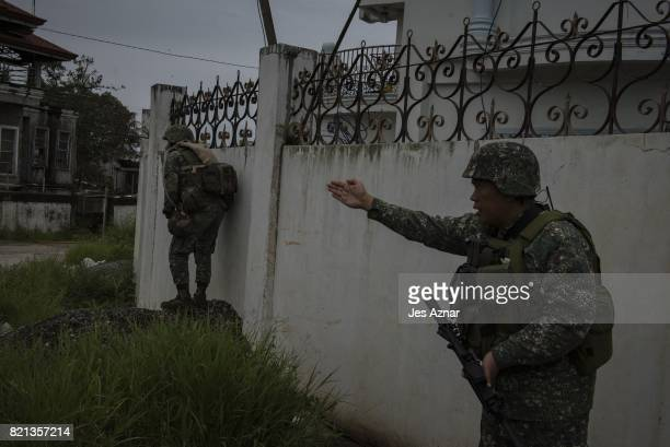 Soldiers take cover from enemy sniper fire as they walk towards the main battle area on July 22 2017 in Marawi southern Philippines The Philippine...