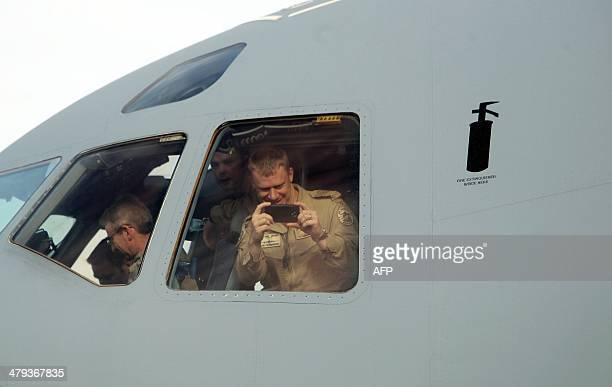 Soldiers take photos from the cockpit of the plane carrying the last of Canada's troops in Afghanistan as they return home at Ottawa International...