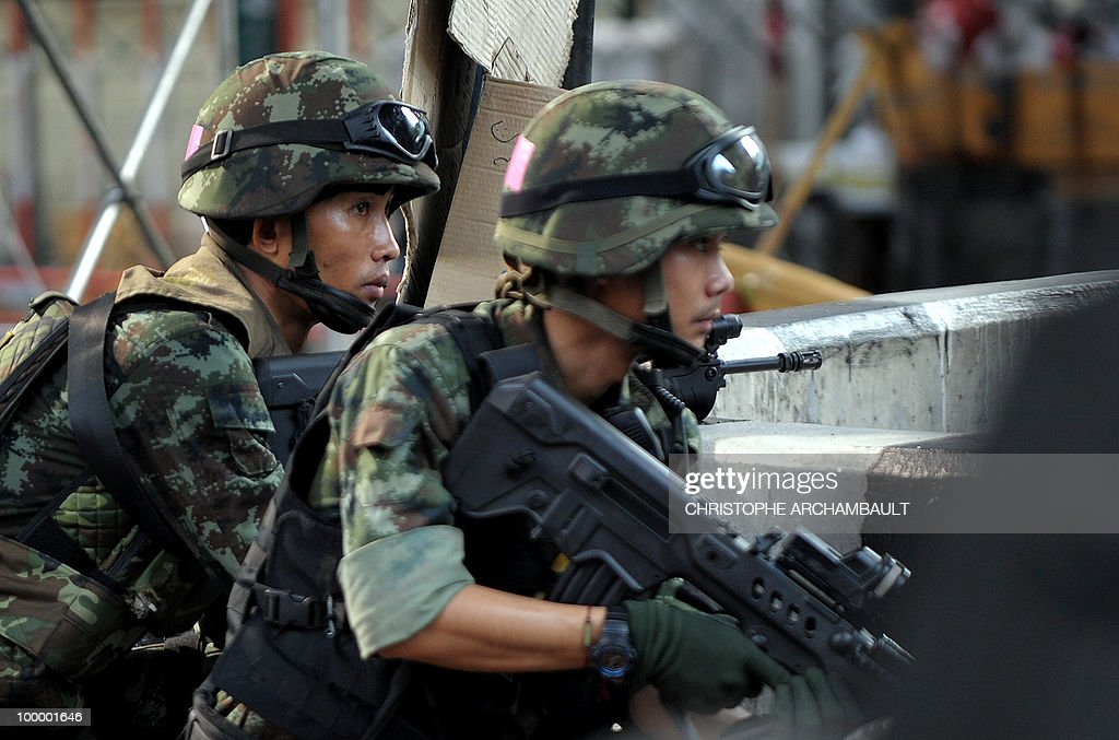 Soldiers take position after gunshots were heard near a Buddhist temple in the heart of an anti-government protest zone, in downtown Bangkok on May 20, 2010. Gunshots rang out near a Buddhist temple in the heart of an anti-government protest zone in Bangkok, and soldiers were advancing on foot along an elevated train track, an AFP photographer saw. Thai security forces stormed the 'Red Shirts' protest camp on May 19 in a bloody assault that forced the surrender of the movement's leaders who asked their supporters to disperse. AFP PHOTO/Christophe ARCHAMBAULT