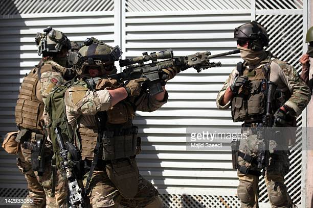 NATO soldiers take position at the site of a gun battle after Taliban militants launched a series of coordinated attacks across the area April 15...